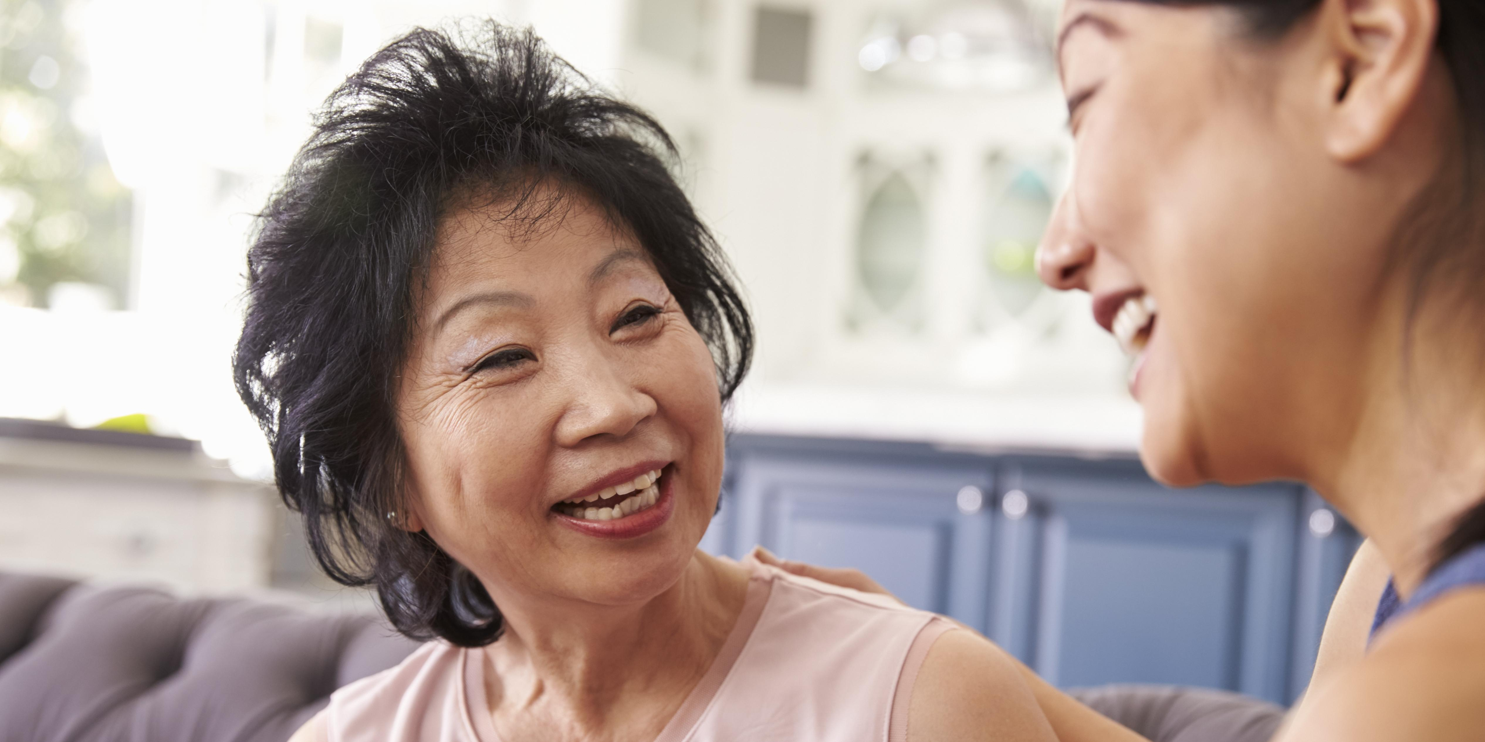 Caregiver and family member laughing with each other.