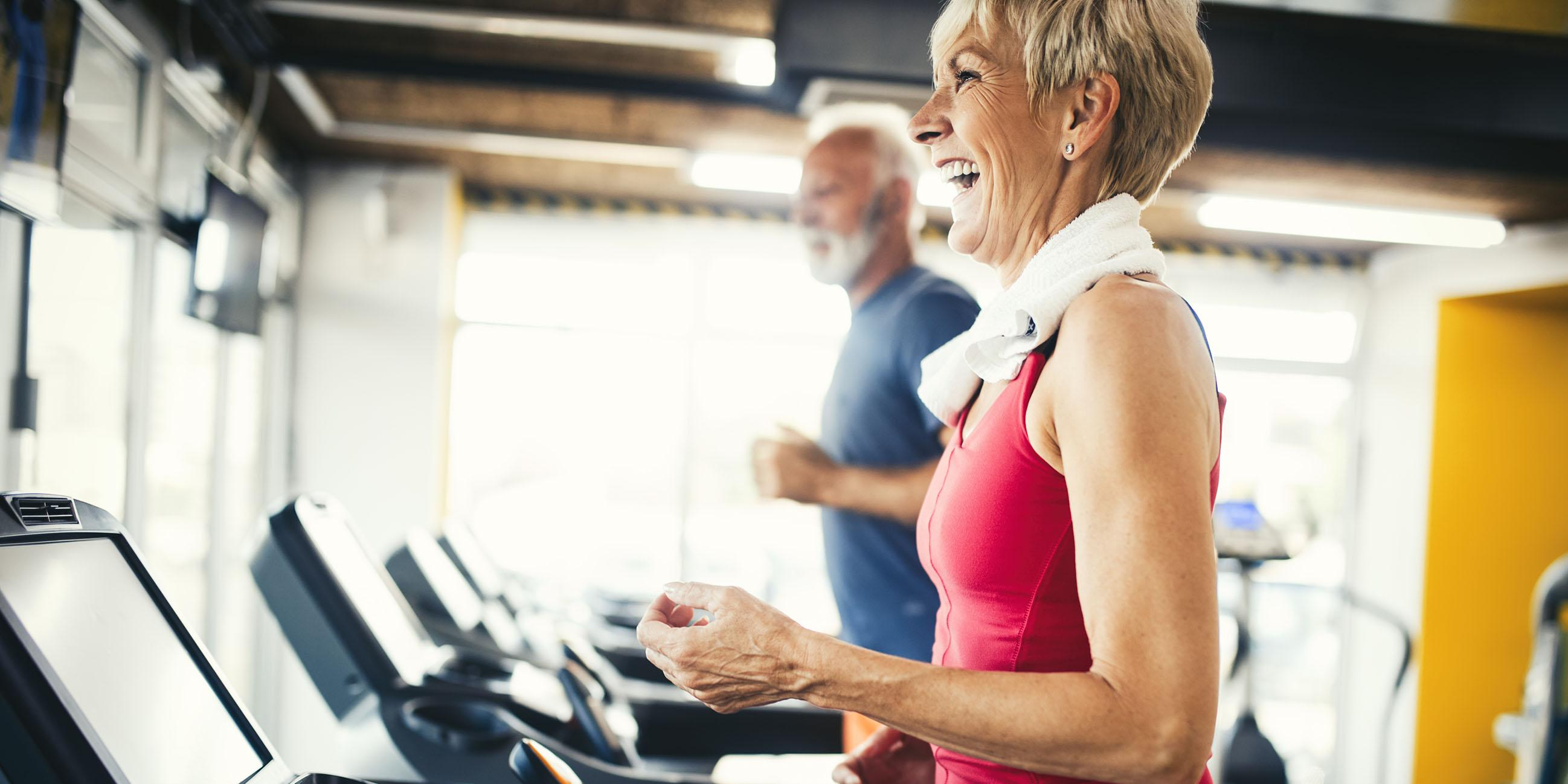 Woman smiling while running on a treadmill.